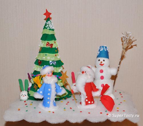 ...поделку - снежная полянка с украшенной новогодней елочкой, снеговиком, Снегурочкой с Дедом Морозом, зайчиками.